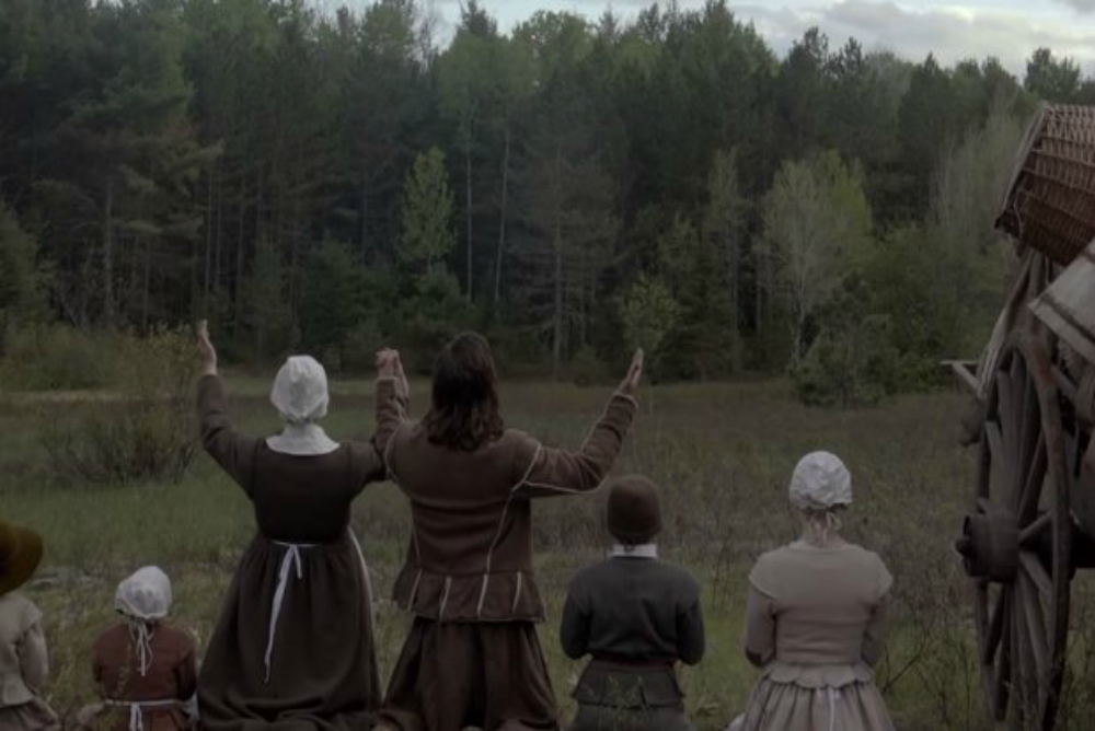 A screenshot from The Witch: A Puritan family kneels before the dark forest and raises their hands in prayer.