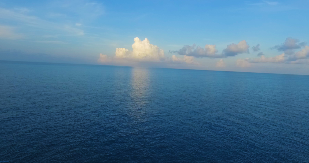 View of the calm blue Atlantic ocean with clouds above the horizon.