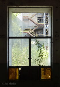 A photo taken looking a broken window in a factory. Green bushes and metal stairs are in view.