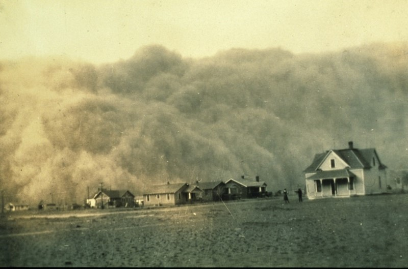 Image of a huge dust storm approaching behind a line of houses.