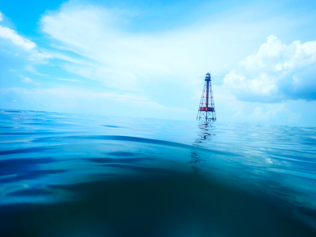 Deep blue water in the foreground, with a beacon rising above the water in the distance.