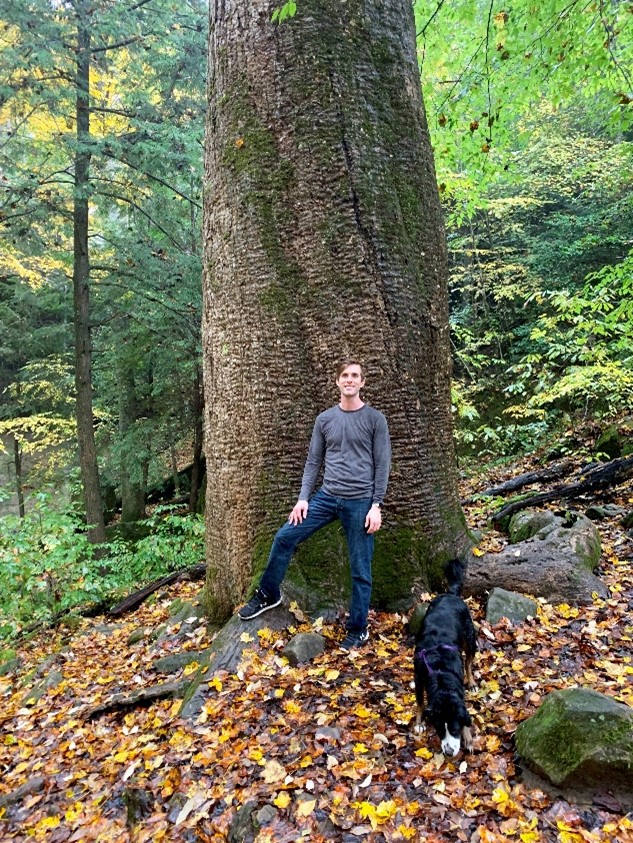 A photo of Nicholas Reich standing in front of the base of a 150-foot tall tree in the forest, with a black dog nearby.
