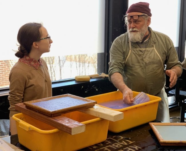 Master Papermaker Robert Possehl teaching a student how to make paper.