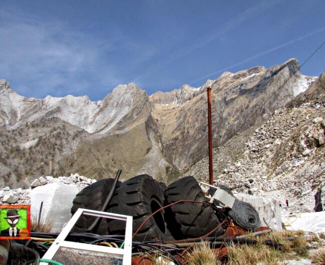 Piles of trash, including old tires, in the foreground; the Alps in the background.