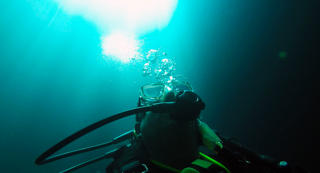 Image of a diver rising toward the light, with bubbles.