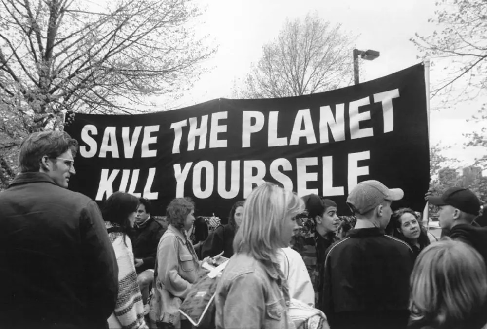 """A black and white image of a crowd with a banner reading """"Save the Planet, Kill Yourself."""""""